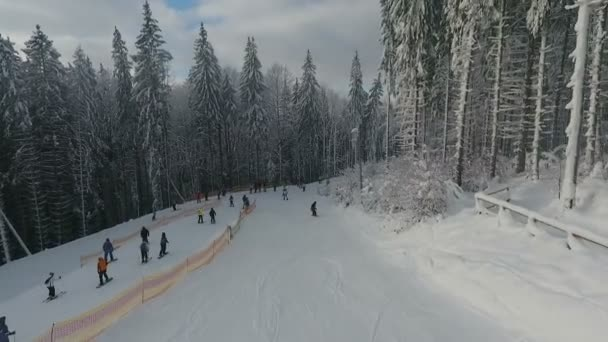 Lyžaři a snowboardisté jezdí na sjezdovce v horském středisku na pozadí zasněžené zimní