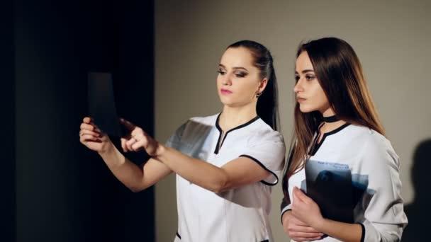 Dvě ženské ženy lékaři při pohledu na rentgen v nemocnici. Lékař radiolog
