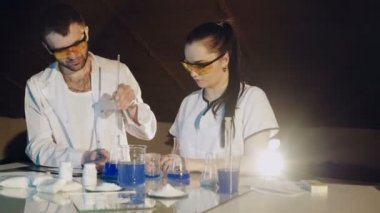 Two Technologists or scientist working in a chemical laboratory doing experiments with colorful solutions in beakers and test tube.