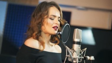 Beautiful woman singing into a large microphone. Professional recording studio.