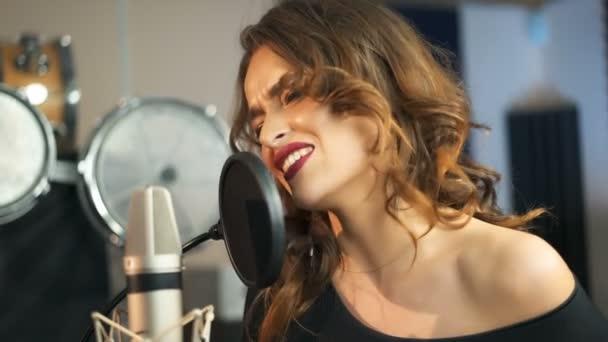 Fiatal énekesnő felvétel album a professzionális stúdióban. Nő énekel egy dalt zenei stúdióban.