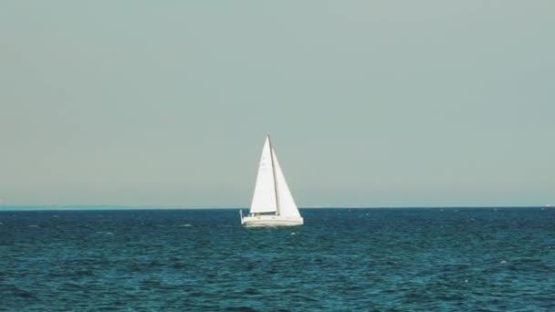 bílá plachetnice pluje na moři daleko od pobřeží v létě. Zpomalený pohyb