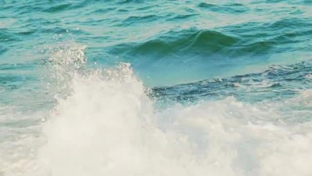 vysoké vlny tyrkysové barvy narážejí na skály a mění se v pěnu. Zpomalený pohyb