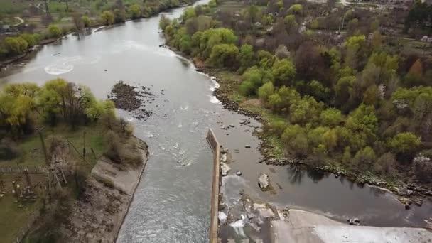 Blick auf die beiden Ufer des Flusses und der Kläranlage im Sommer aus luftiger Höhe. Vorstadtlandschaft aus der Vogelperspektive. Kamerabewegung runter. Luftaufnahme.