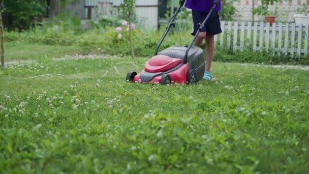 Mladý chlapec seká trávu sekačkou v létě. Venkovní sezónní práce domácnosti