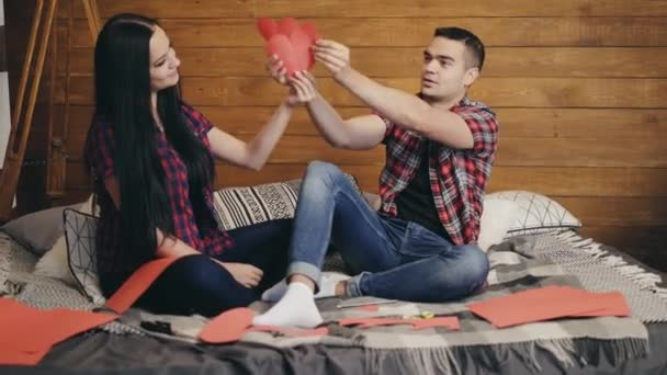 Enamored are sitting on the bed and holding red paper hearts in their hands and playing. Love story.