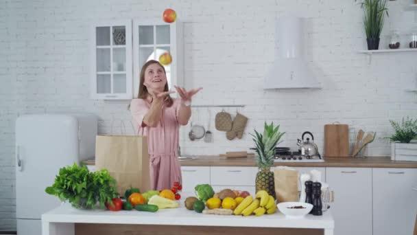 Mladá žena v kuchyni. Žena se baví v kuchyni při vaření