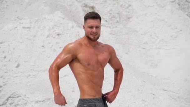 Bodybuilder-Athlet zeigt Muskeln. Schöner Mann mit großen Muskeln posiert vor der Kamera