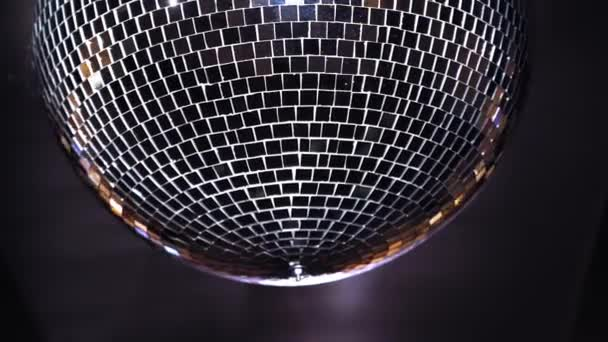 Diskotéka s jasnými paprsky. Zblízka barevné disco koule světlo visí na stropě