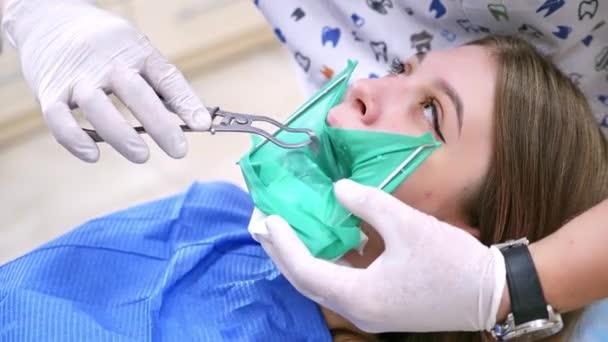 Patient im Zahnarztstuhl. Schöne junge Frau mit Zahnbehandlung beim Zahnarzt