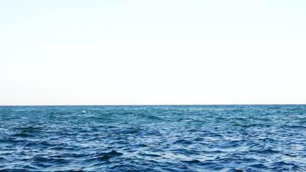 Vlnitá hladina mořské vody. Pohled na modré pozadí moře