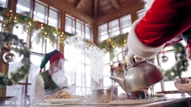Elfové kolem Santa Clause. Santa Clause a elfové mají vánoční hostinu
