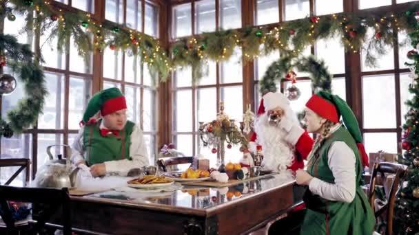 Rodinná večeře o Vánocích. Santa Claus slaví s elfy u stolu