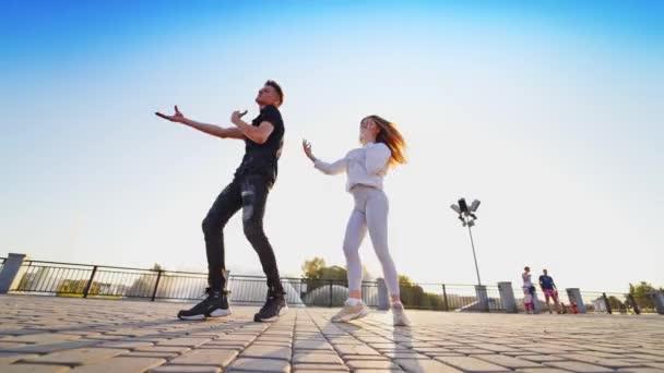Tanzendes Paar in der Nähe des Brunnens. Fröhliche junge Liebespaare tanzen im Freien