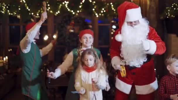 Děti tančí a zpívají o Vánocích. Šťastné děti si hrají se Santa Clausem a elfy