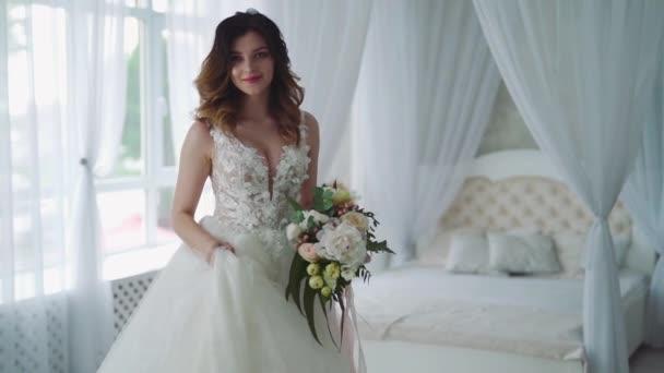 Gyönyörű fiatal menyasszony a hálószobában. Gyönyörű fiatal menyasszony fehér esküvői ruha beltérben