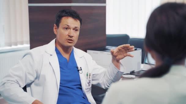 Arzt im Gespräch mit Patient. Charmanter Arzt berät Patientin