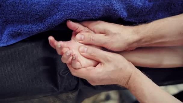 Körperpflege bei Wellness-Behandlungen. Frau genießt eine Handmassage im Wellnessbereich