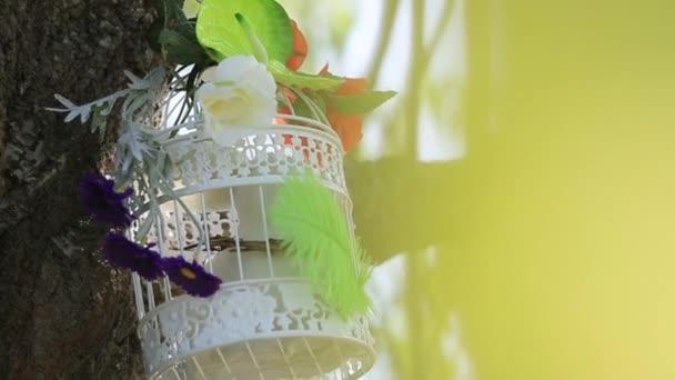 v parku na větvi věšící bílou ptačí klec s krásnou kyticí květin