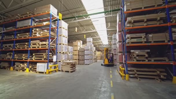 Egy narancssárga elektromos rakodó vezet a polcok között a raktáron lévő árukkal. Munkafolyamat a vállalatnál.