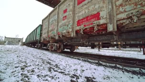 Řada vícebarevných kontejnerů pro nákladní jízdu podél kolejnic na nádraží a zastávky na pozadí země pokryté sněhem. Pohled na dno. Detailní záběr.