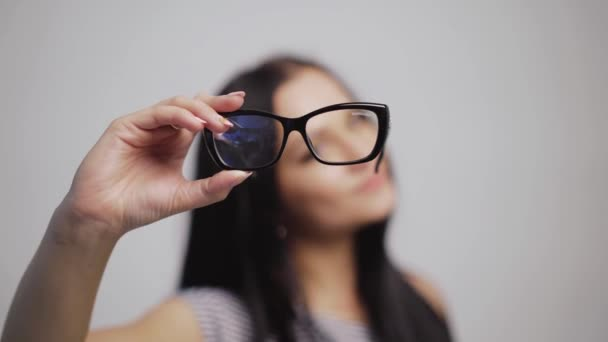 Hezká žena ukazuje zleva doprava stylové brýle a nasazuje je s rozmazaným pozadím. Módní brýle v ruce tmavovlasé ženy. Detailní záběr