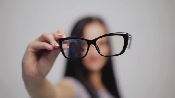 Módní brýle zblízka na rozmazaném pozadí ženy. Žena ukazuje a pak si nasadí nové brýle v černém ráfku.