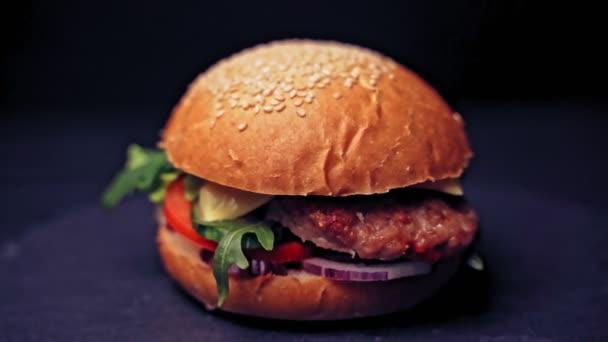 Velký hamburger s hovězí kotletou, rajčaty, houbami a okurkami s roztaveným sýrem se otáčí na dřevěné desce na tmavém pozadí.