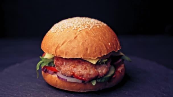 Velký hamburger s hovězím řízkem, rajčaty, salát s roztaveným sýrem se otáčí na dřevěné desce na černém pozadí.