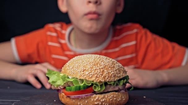 chlapec ochutnává chutný velký burger, fast food