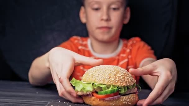 A fiatal boldog tinédzser finom hamburgert eszik. Finom grillezett burger