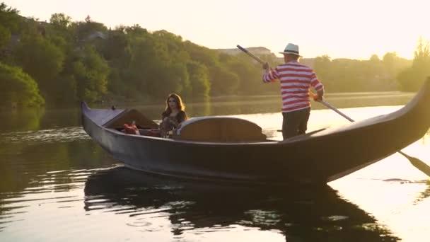 Schöne Frau sitzt in einem Boot und ein Mann rudert mit dem Ruder auf dem natürlichen Hintergrund bei Sonnenuntergang. Traditionelles venezianisches Ruderboot mit dem Gondoliere und einer Frau im Abendfluss.