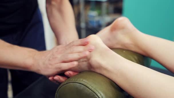 Egy profi masszőr kezei, amint egy női ügyfélnek masszírozza a lábait. Terapeuta masszírozza a női lábakat, amik az ovális görgőn fekszenek. Közelkép.