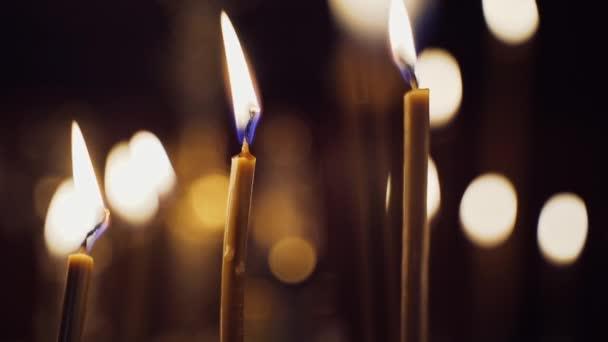 V kostele jasně plály svíčky. Hořící svíčky na rozmazaném pozadí se světlými skvrnami. Detailní záběr