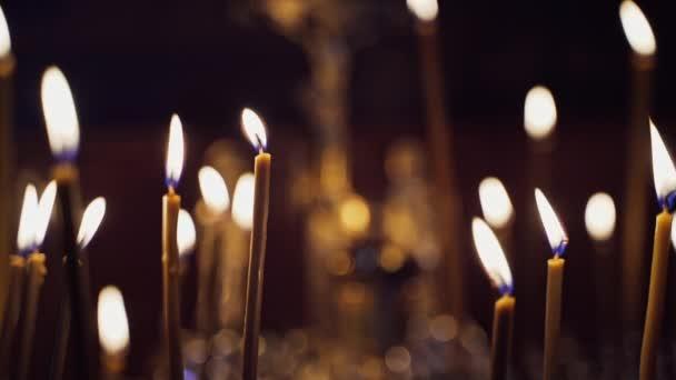V nočním chrámu hořela spousta svíček. Abstraktní pozadí svíček. Žluté plameny svíčky zářící na rozmazané tmavé pozadí v kostele.