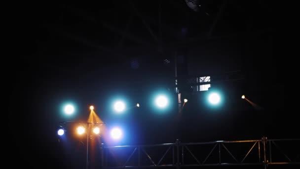 Színes fények a vetítőktől, amik fényesen ragyognak a klubban. Villogó sugarak kék és narancssárga színekben a reflektorfényből a sötét előadóteremben.