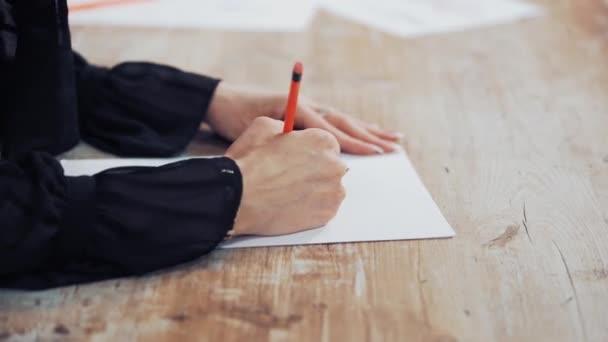 Dressmaker rajzol egy kreatív design egy modern ruházat beltéri. Egy fiatal szabó női kezei a fa asztalon egy ceruzával. Női hobbi.
