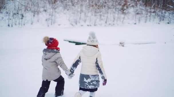 Back view of two children are walking together in the snowy forest. Little kids hold their hands and go through the white snow outdoor. Slow motion.