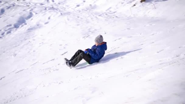 Junge, der Spaß hat und von einem Hügel reitet. Frost Wintersaison.Netter kleiner Junge mit Untertasse Schlitten im Freien an einem Wintertag und trifft seinen Freund oder seine Schwester oder Bruder, fahren die Hügel hinunter, Winterspiele und Spaß. Zwei Kinder beim Rodeln angefahren.