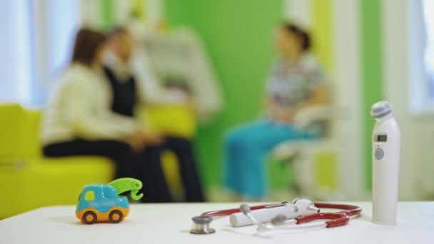 Thermometer, Phonendoskop und ein Spielzeugauto stehen drinnen auf dem Tisch. Spielzeug und medizinische Geräte vor dem Hintergrund, dass Eltern gegen den Arzt im Zimmer sitzen.