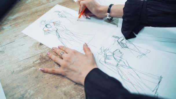 Eljárás rajz vázlatok egy modell ruha papíron egy női szabó. Professzionális tervező rajzol illusztrációk a jövőbeli ruhák egy ceruzával az asztalon atelier.