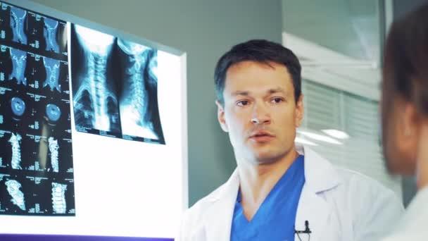 Doktor Rüde zeigt der Frau die Problemzone auf dem Röntgenbild. Wirbelsäulentomographie hängt am Whiteboard und der Arzt diskutiert die Ergebnisse.