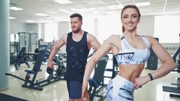 Muž a žena pózují se svým atletickým tělem ve fitness centru. Atraktivní pár s svalnatými těly dělat cvičení v tělocvičně.
