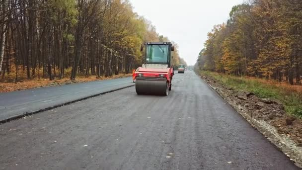 Heavy equipment while building an asphalt road. Steamroller pressing new asphalt in highway in autumn. Road works on natural background.