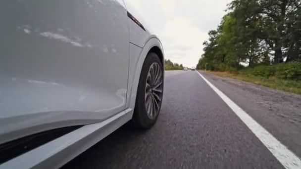 Közelkép az autó és a kerék oldalsó részén az út mozgatásához. Luxus fehér autó kereke lassan kanyarodik az aszfaltozott úton.
