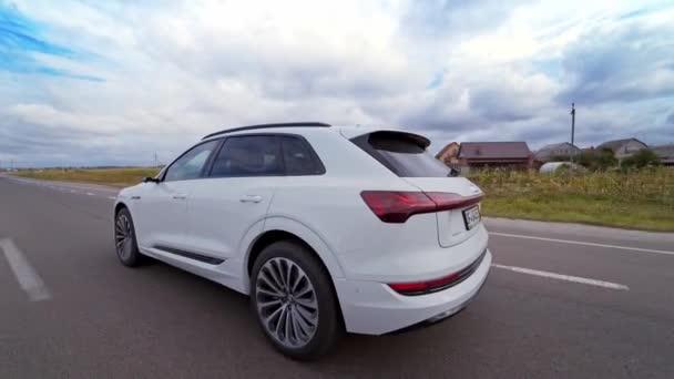 Boční pohled na krásné bílé audi na dálnici. Luxusní automobil na přírodním pozadí. Zpomalený pohyb.
