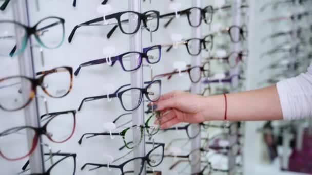 Ženská ruka vybírá brýle na stánku uvnitř. Žena bere nové brýle v obchodě s optikou.