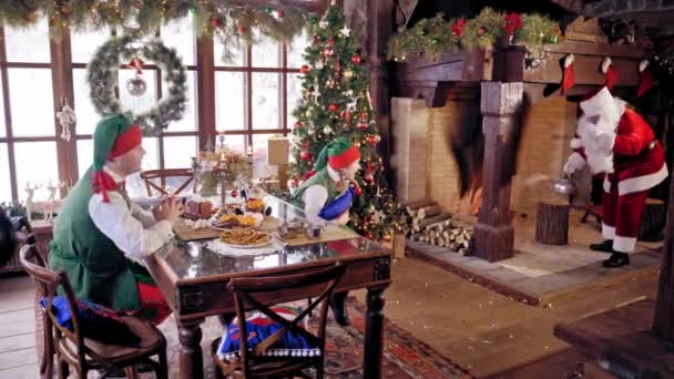 Elves sitting at the table on beautifully decorated background for Christmas. Santa Claus with hot kettle coming to the table.