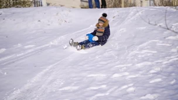 Junge rutscht auf Schnee. Kleine Kinder rodeln im Winter fröhlich auf Plastikschlitten vom weißen Hügel. Zeitlupe.