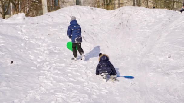 Jungen mit Plastikschlitten auf einer Rutsche im Winter. Rückansicht von Kindern auf Schnee Hintergrund. Zeitlupe von Jungen, die im Freien den verschneiten Hügel hinaufsteigen.